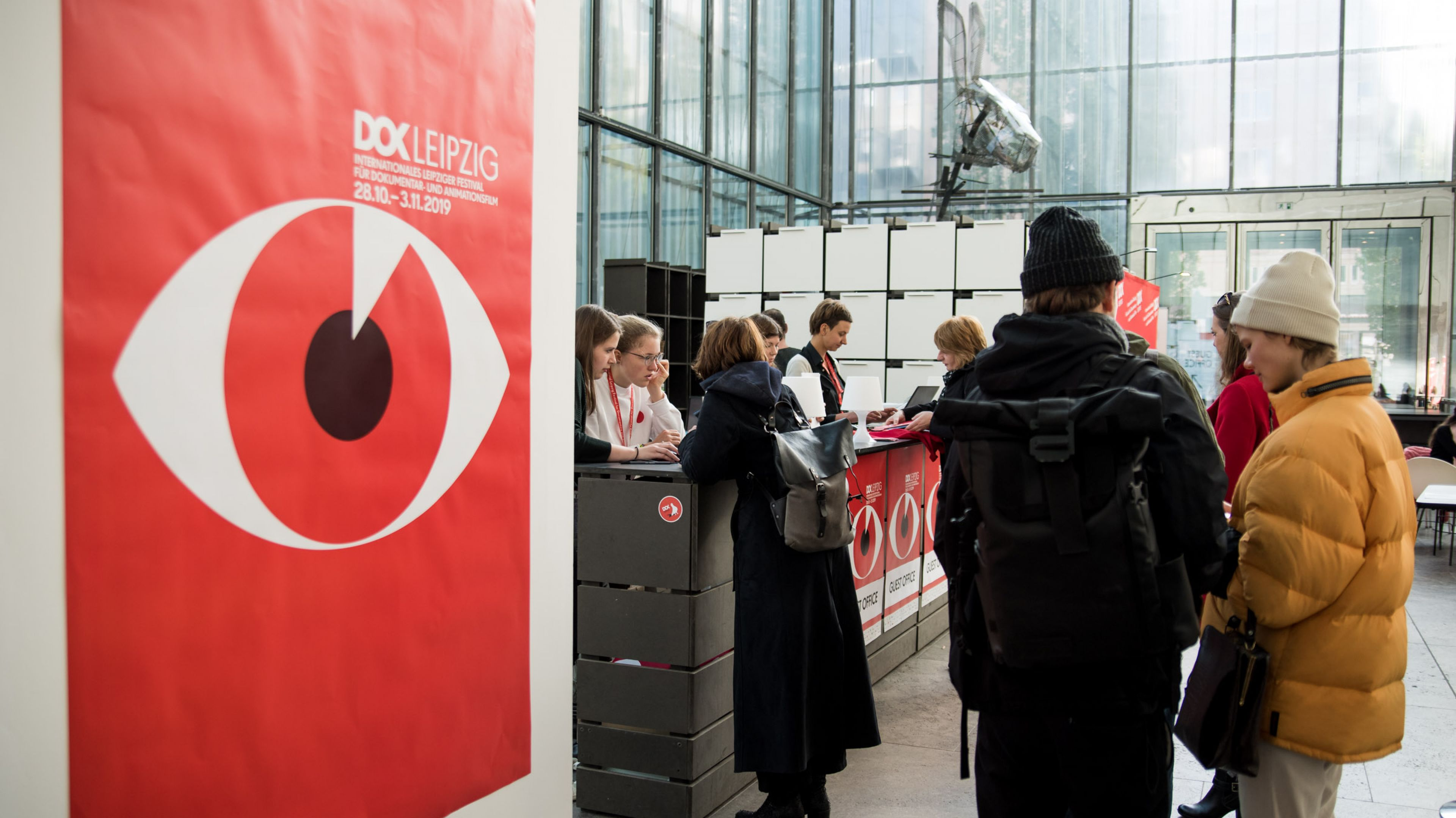 Junge Menschen stehen in einer Schlange vor dem Schalter im lichtdurchfluteten Gästebüro an. Links ist ein Plakat mit dem Festivalmotiv, einem Auge vor rotem Hintergrund, zu sehen.