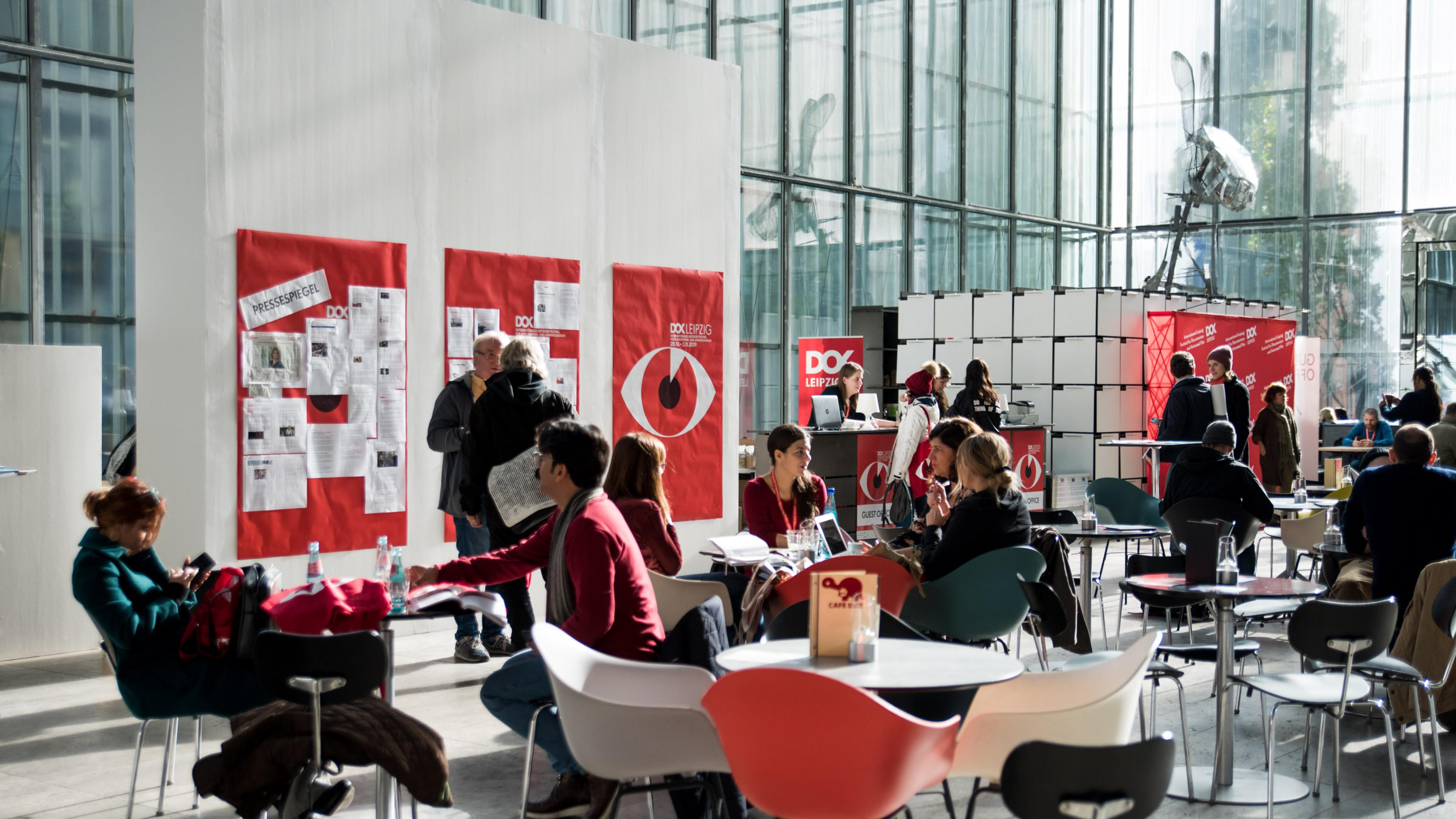 Mehrere Personen sitzen an Cafétischen, im Hintergrund Wände mit zahlreichen DOK Postern.