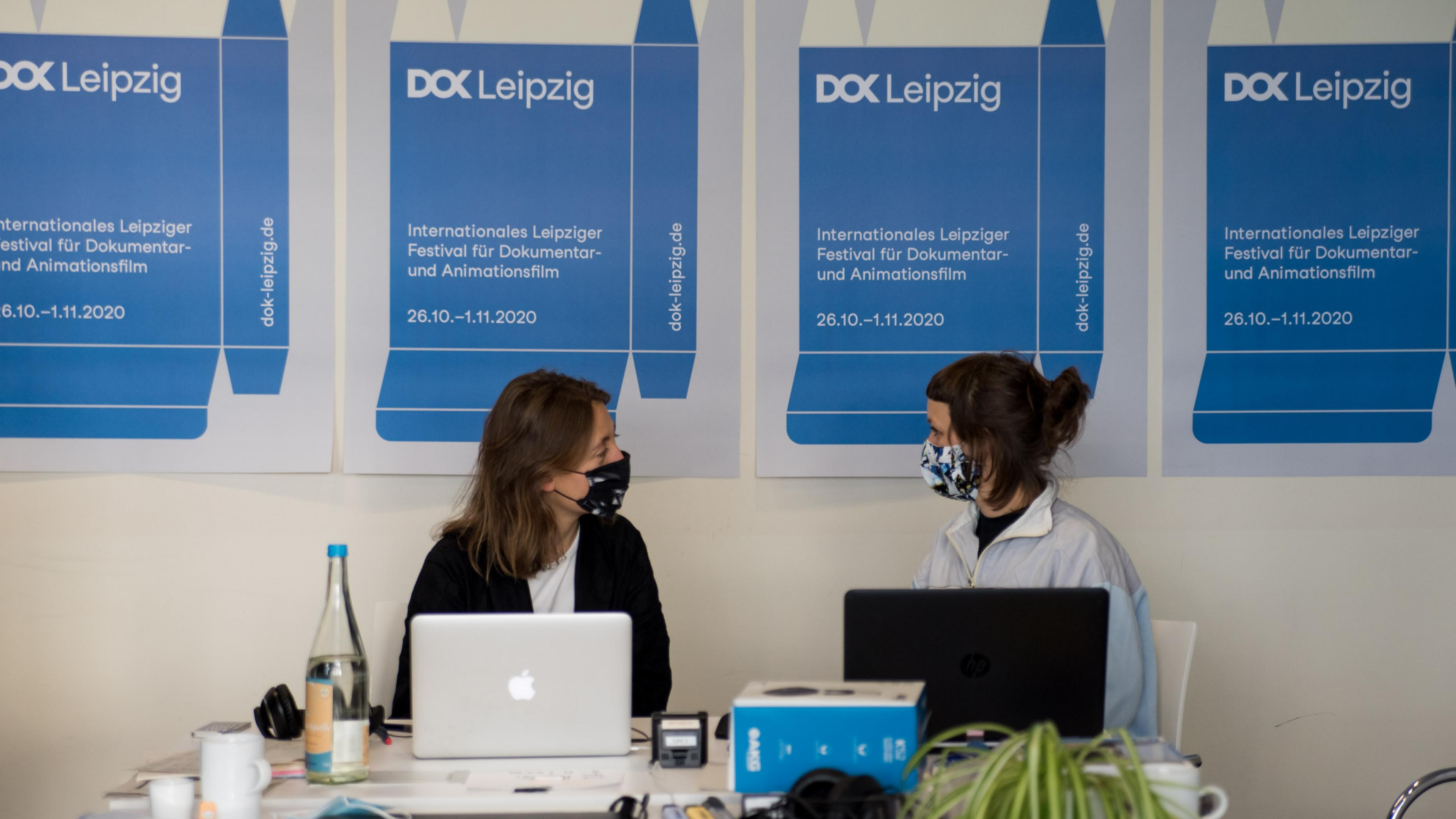 A row of DOK Industry posters on the wall, in front of them two women with masks are sitting next to each other in fron of their laptops and look at each other