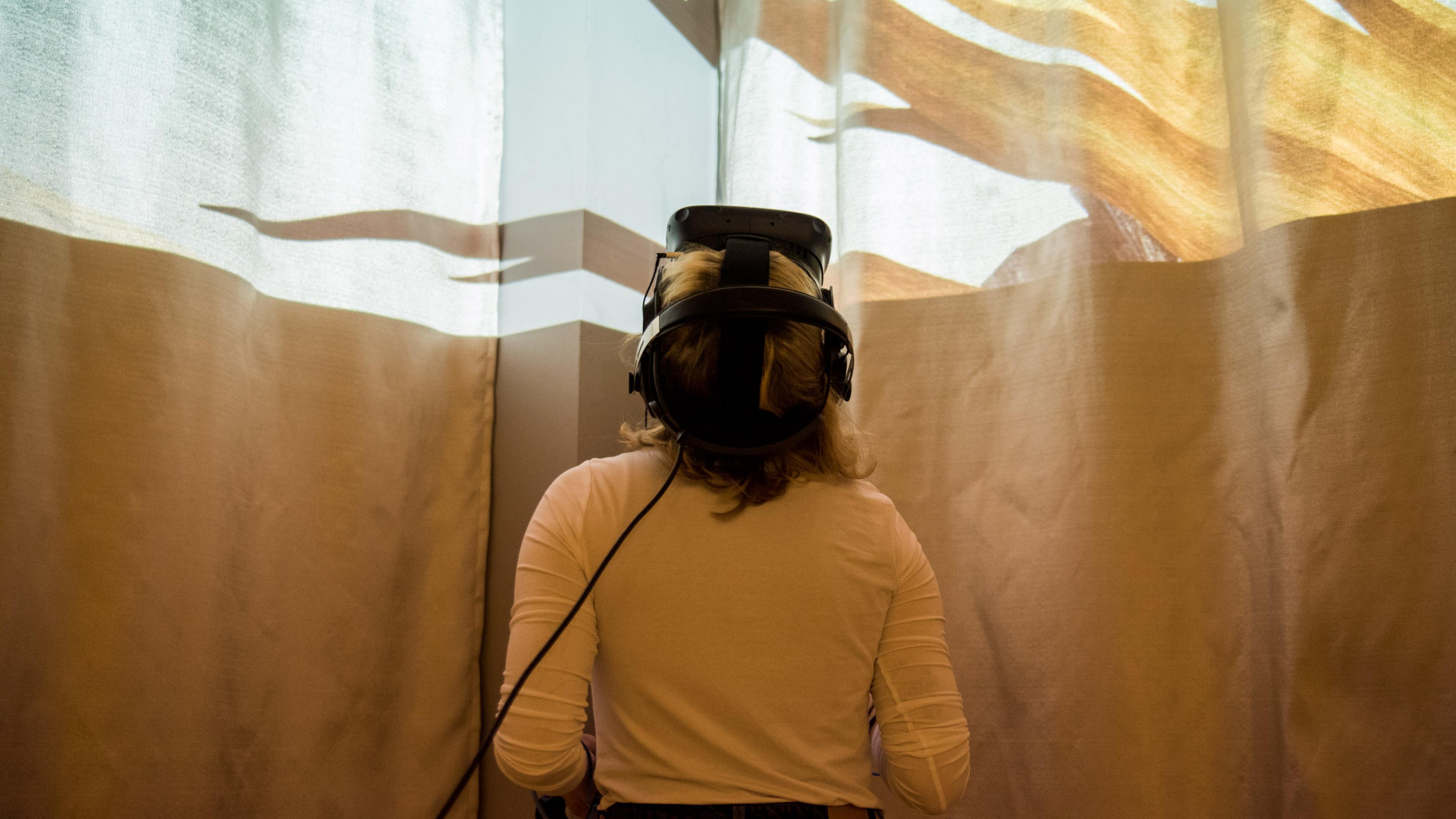 Ein weibliche Person mit VR-Brille legt ihren Kopf in den Nacken, oben im Bild erscheint eine Lichtinstallation.