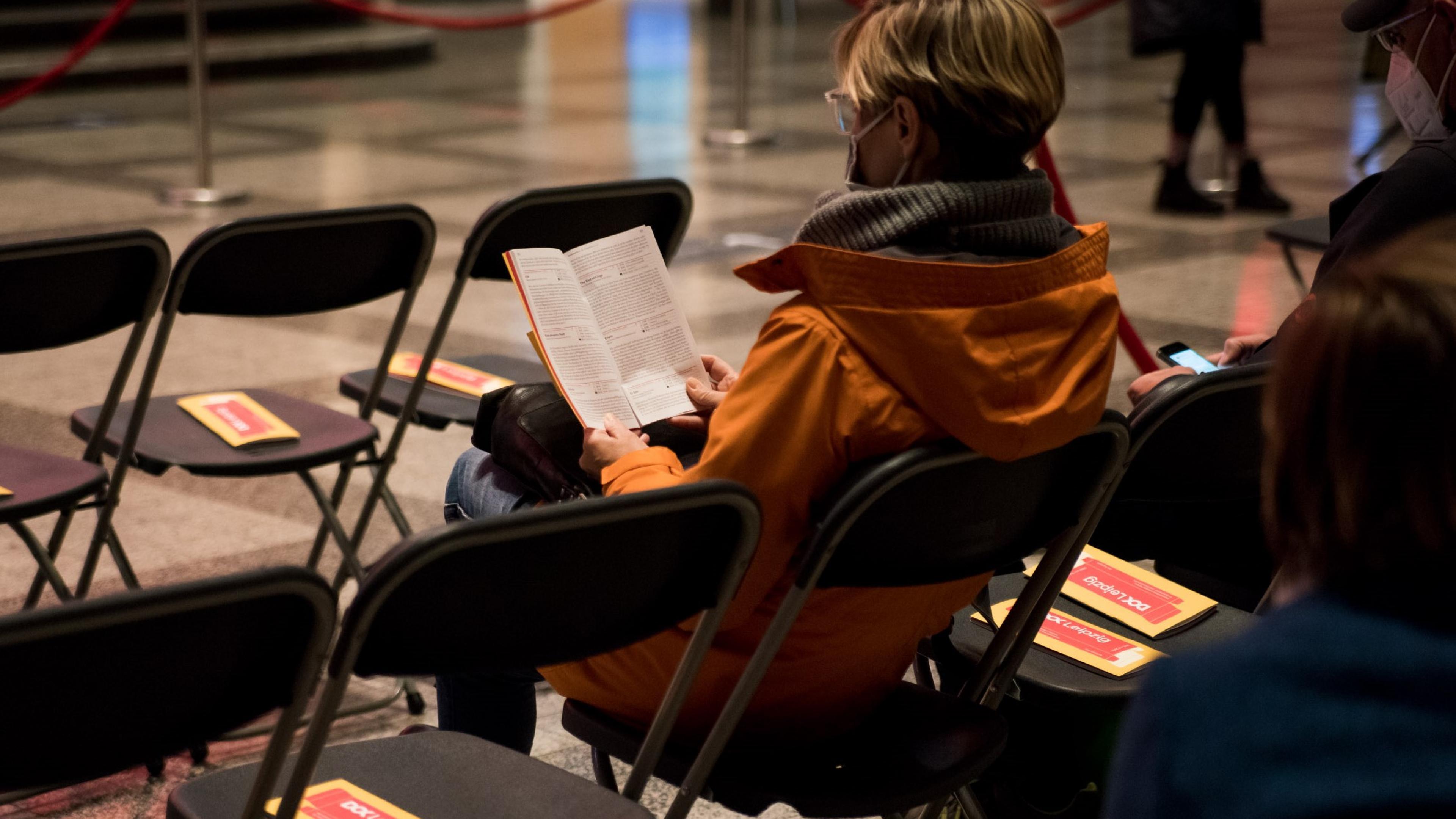 Eine Frau mit Maske sitzt auf einem Stuhl und liest in einem DOK Leipzig Programmheft. Um sie herum stehen mehrere Stühle in Reihen mit Programmheften auf den Sitzen, neben ihr sitzt ein Mann mit Maske