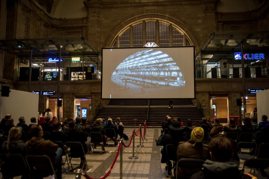 A screening in the big hall of the Leipzig main station, a big audience is watching a train on the screen